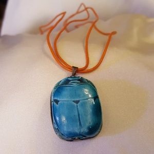 Jewelry - A light blue scarab on an orange cord